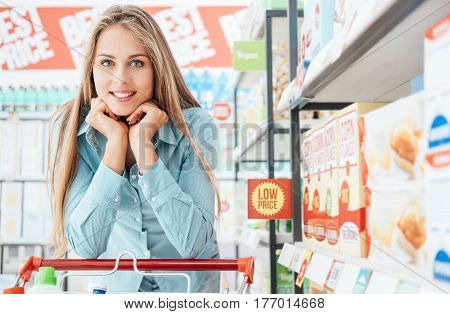 Young smiling woman enjoying shopping at the supermarket she is leaning on the full cart with hand on chin