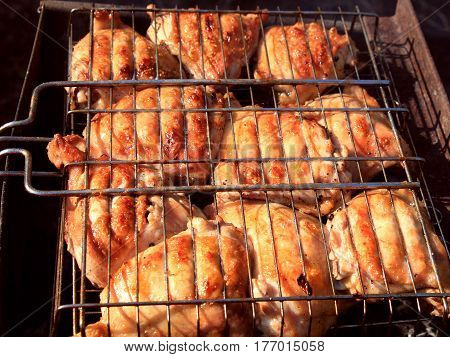 Meat grill. The chicken pieces are cooked on the grill. Rich, rosy, they spread the enticing aroma of the flame-broiled meat