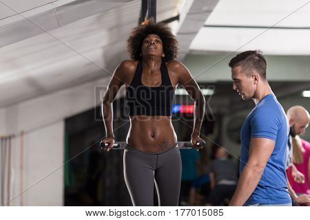 african american athlete woman workout out arms on dips horizontal parallel bars Exercise training triceps and biceps doing push ups with trainer