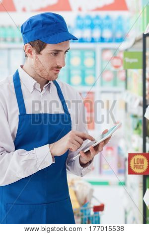Supermarket Clerk Working With A Tablet