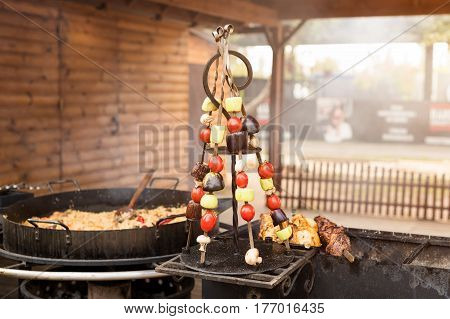 Grilled vegetables on metal skewers. Street food.