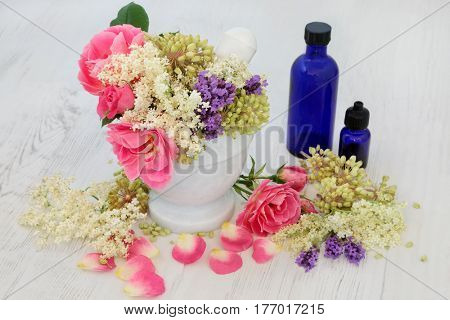 Medicinal flower selection of rose, elderflower, lavender herb and angelica seed heads used in natural alternative herbal medicine with aromatherapy bottles and mortar with pestle.