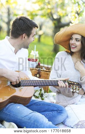 Young couple in love at picnic in spring blossom garden. Happiness and love concept