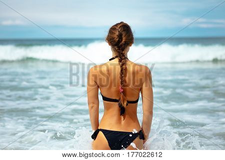 Outdoor summer portrait of young elegant fit woman standing backwards and going into sea to swim in waves near tropical beach. Sports girl in bikini enjoy nature paradise summer vacation in Thailand