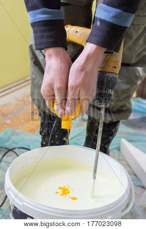 Man gives yellow coloring to white a paint for painting