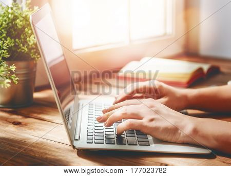 Woman person working on the laptop while sitting at the desk.
