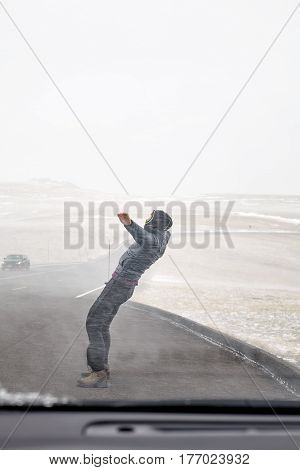 Woman Tries To Stand Against Snow Flurry.