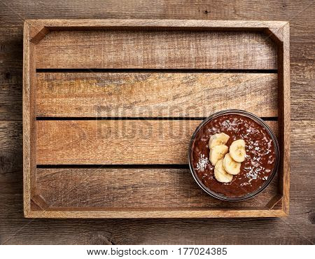 chocolate chia pudding with banana in a glass bowl on gray concrete background