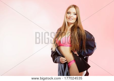 Clothing fashion people concept. Attractive woman wearing lingerie. Studio shot of lady with pink underwear and black big shirt.