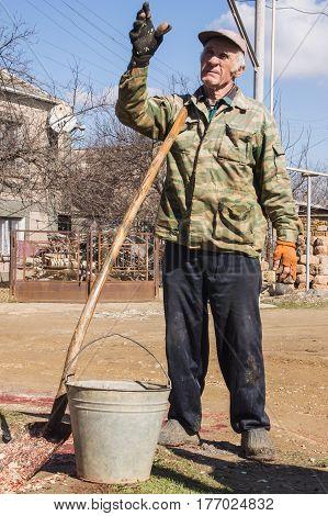 Elderly Russian Farmer With Bucket