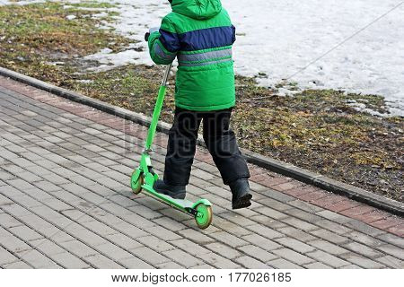 Walks in the fresh air. Kid riding a Kick scooter on the pavement in the cold season.
