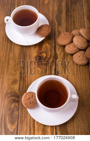 Two cups of hot black tea and oaten cookies on a wooden table.