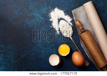 Ingredients and utensils for baking. Spoon with flour eggs rolling pin baking paper on a blue background. Top view selective focus copy space