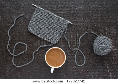 Piece of grey knitting on a kneeting needle and a cup of hot coffee with milk on black background. Shot from above.