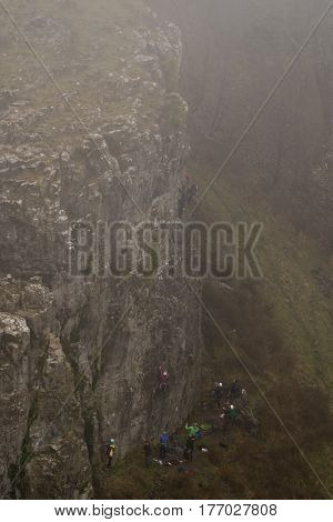 Group of rock climbers in fog at Cheddar Gorge. Team of climbers ascend cliff in Somerset UK in one of Britain's most impressive areas of natural beauty