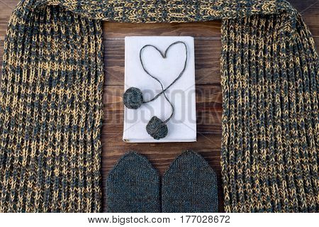 Winter still life with a scarf, mittens, a book and a heart made of woolen year on a wooden table. Shot from above.