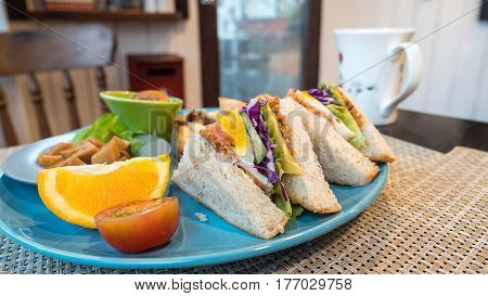 Closeup club sandwich breakfast made from fried egg tomato cheese and lettuce with orange bread and mushroom on blue dish (Selective focus)
