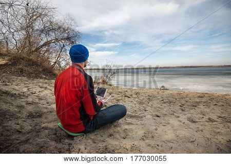 Man Attentively Monitors The Flight Of The Drone Over The Surface Of The Water