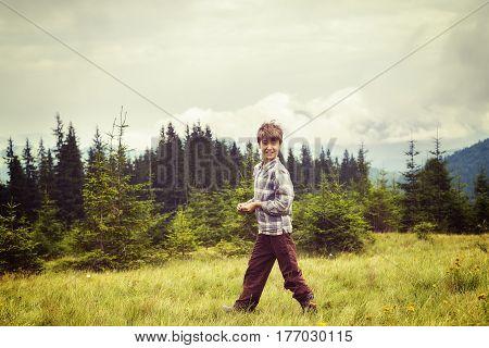 Funny Boy Is Walking Along The Green Alpine Meadow