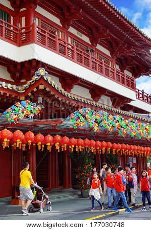 Singapore, Singapore - February 11, 2017: People walk in the Chinatown, decorated for China New Year, alongside the Buddha Tooth Relic Temple on sunny day in Singapore.