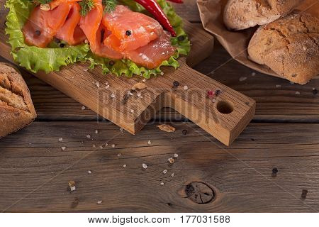 Slices of smoked salmon with dill chilly pepper tomatoes and bread on rustic wooden background.