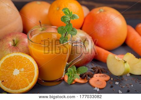 Glass of homemade juice or smoothie fruits and vegetables. Fresh carrot apple pumpkin orange grapefruit on dark table. Healthy eating food dieting detox and vegetarian concept.