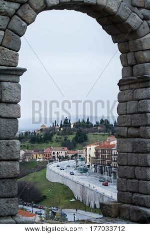 A view through the arch of famous ancient roman aqueduct of Segovia to town and streets Castille and Leon Spain.