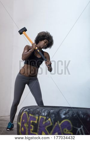 Sledgehammer Tire Hits african american woman workout at gym with hammer and tractor tire