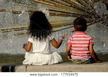 Oslo Norway - July 22 2014: Children sitting at the edge of the fountain near the Royal Palace in Oslo.