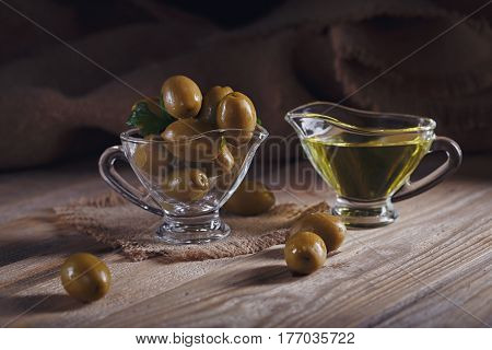 Premium extra virgin olive oil and green olives with fresh herbs on rustic wooden background.