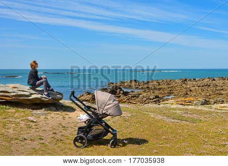 Mother strolling with a baby looks at the Atlantic Ocean