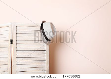 Hat Hanging On Wooden Folding Screen On A Beige Background