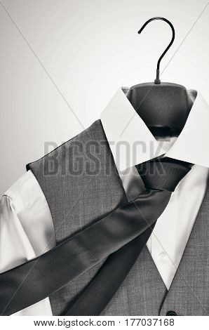 Mens grey waistcoat and tie over a white tailored shirt hanging on a velvet hanger in black and white.