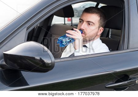 Man drinking bottle of water seated in car
