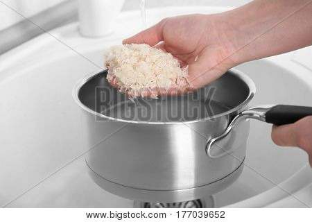 Woman rinsing rice in saucepan with water