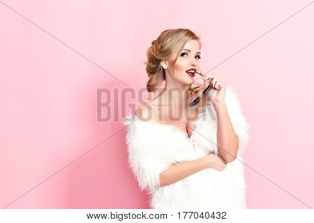 Portrait of glam girl in white fur and sunglasses on pink background. Fashion photo
