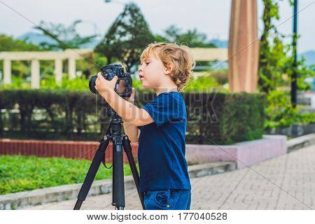 The Toddler Boy Takes Pictures On A Camera On A Tripod