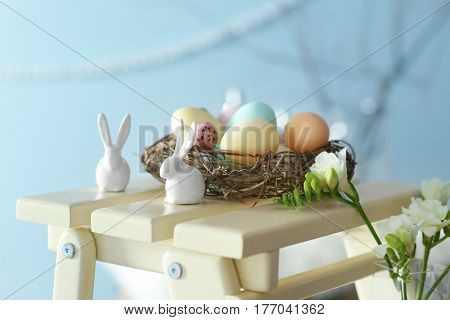 Rabbits and nest with painted eggs on decorative wooden stool