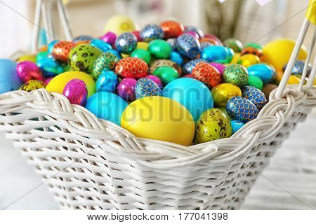 Easter basket with colorful eggs on table, closeup