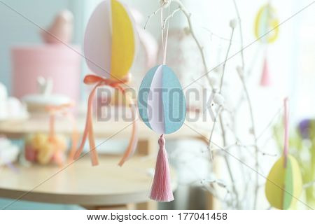 Easter tree made of painted pussy willow and colorful paper eggs on blurred background