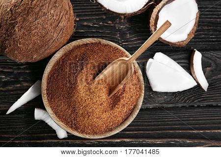 Bowl and scoop of brown sugar with coconut on wooden background