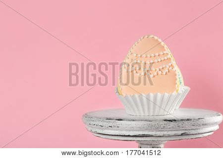 Dessert stand with creative egg shape Easter cookies on pink background