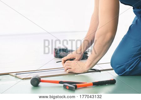 Male worker hands installing laminate flooring