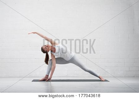 Young flexible woman practicing yoga indoors. Fit girl wearing white sportswear exercising on grey mat.