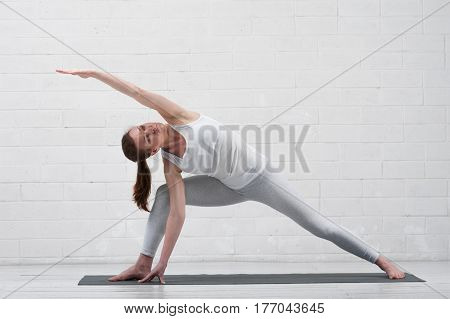 Young flexible woman wearing white sportswear practicing yoga indoors. Fit girl working out on mat