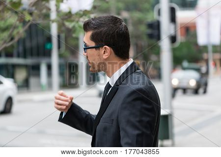 Businessman talking to someone outside the frame, city landscape