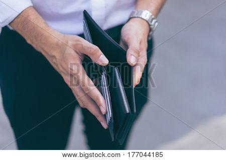 Man standing holding black wallet empty of money