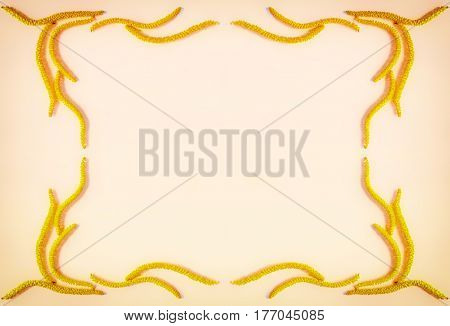 Abstract floral composition vintage frame of yellow flowers earrings hazel on the background of the color golden edge with space for text. Flat lay top view