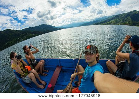 PHEWA LAKE POKHARA NEPAL 27 JUNE 2013: Group of tourists with photo cameras on the boat
