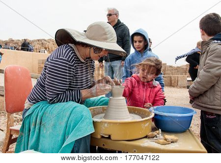 Participants Of Festival Teaches Girl To Make Pitcher Of Clay